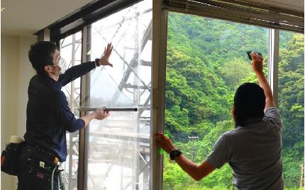 窓フィルムを職人が施工している様子