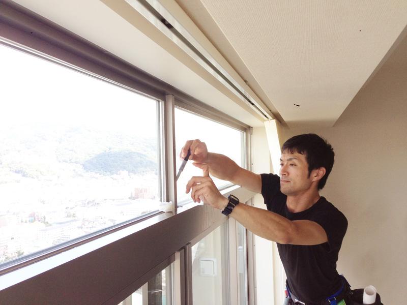 ビルの窓フィルムを職人が貼り付け施工している様子